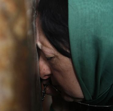 A woman leans against a wall inside Svetitskhoveli cathedral in Georgia's ancient capital of Mtskheta, outside Tbilisi. Georgia marks the 1700th anniversary of Svetitskhoveli cathedral and the 1000th anniversary of its first reconstruction