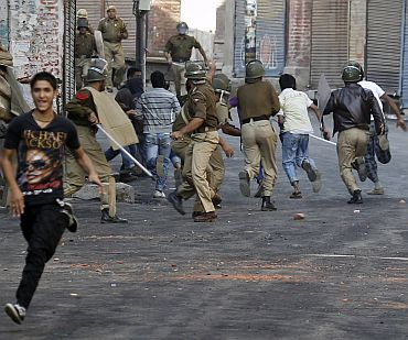 Police chase away Kashmiri protesters during an anti-India protest in Srinagar on October 15. At least 110 people have been killed since June, mostly by police bullets. The protests are the biggest since an armed revolt against Indian rule broke out in Kashmir in 1989