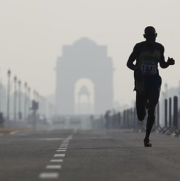 File photo shows Safari Rachid of Rwanda running past India Gate while competing in the men's marathon final during the Commonwealth Games in New Delhi