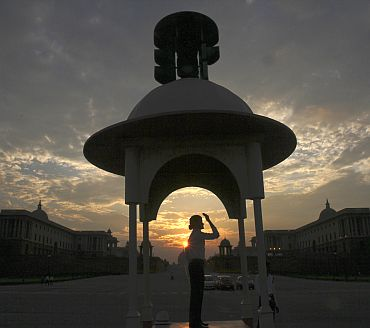 A traffic police woman directs traffic as she is silhouetted against the backdrop of clouds during an evening in New Delhi