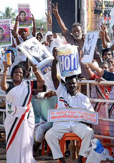 An AIADMK supporter hold up a bottle in a dig at MK Alagiri