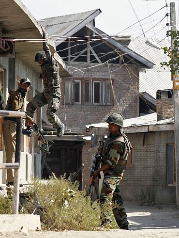 An army soldier climbs down from a residential house during the gun battle