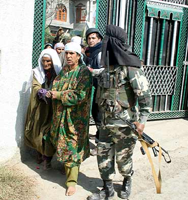 A soldier escorts civilians to safety during the gunbattle