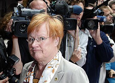 Journalists click photographs as Finland's President Halonen arrives at a EU summit
