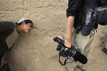 Local boy peeks at a journalist's video camera in Saidon Kalacheh village in Afghanistan