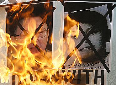 Protesters in Seouol burn portraits of North Korean leader Kim Jong-il and his son during a demonstration demanding the release of two US journalists held in North Korea