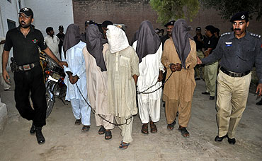 Police escort suspected militants to a prison in Bahawalpur, Pakistan