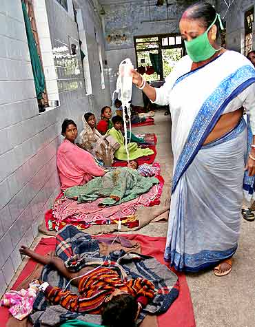An medic tends to a child afflicted with malaria at a hospital in Siliguri, West Bengal