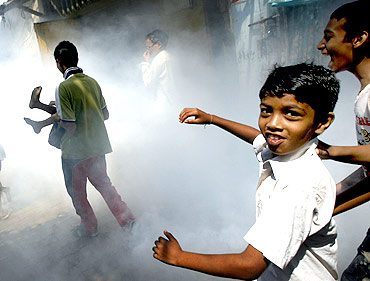 Children play as a health worker fumigates a slum to prevent malaria in Mumbai