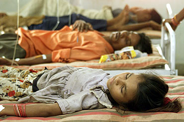Indian flood victims Patients suffering from malaria lie on hospital beds in Alindra, Gujarat