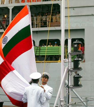Engineers and dock labours watch commissioning ceremony of Indian guided missile frigate warship in Kolkata