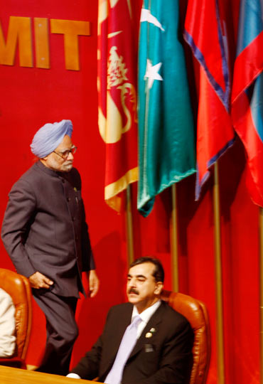 Prime Minister Manmohan Singh walks past Pakistan Prime Minister Yousaf Raza Gilani during the SAARC summit in Colombo