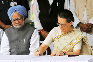 Congress president Sonia Gandhi watched by PM Singh while filing her nominations