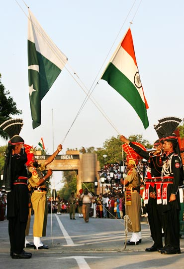 Pakistani Rangers and BSF jawans lower their respective country flags during the daily parade at Wagah border
