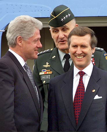 US President Bill Clinton with General Hugh Shelton, Commander of the Joint Chiefs of Staff and Secretary of Defense William Cohen (R) upon their arrival at the Norfolk Naval Base