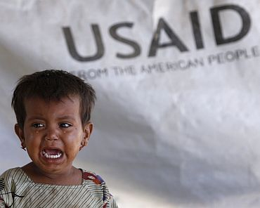 Three-year-old Phaphol cries as she sits in her family's tent, with a weather sheet donated by USAID, while taking refuge on an embankment at Chandan Mori village in Dadu in Pakistan's Sindh province