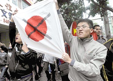 Chinese students hold a defaced Japanese national flag during their anti-Japan demonstration in Lanzhou in Gansu province