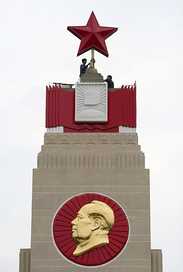 Workers at a monument with an emblem of Mao Zedong