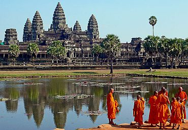 Buddhist monks in front of the reflection pool at Angkor Wat, Cambodia.