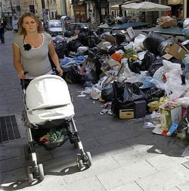 A woman pushes a stroller near a pile of garbage in downtown Naples