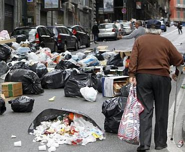 A man walks on a street full of rubbish in Naples