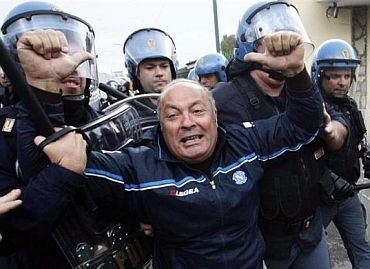 A man tries to block the way of the police during a protest in Terzigno