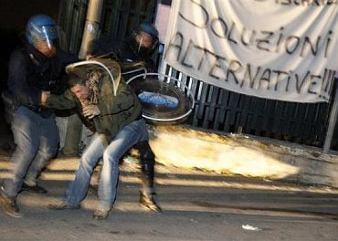 Riot policemen arrest a protester during violent overnight protests against the opening of a new waste dump in Terzigno