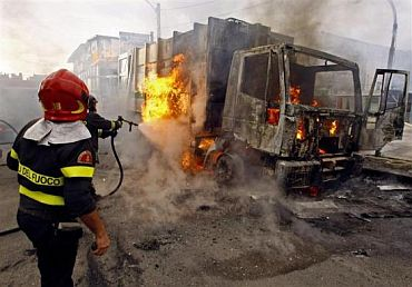 Firemen extinguish a burning truck after violent protests against the opening of a new waste dump in Terzigno