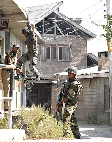 A soldier climbs down from a residential house during a gunbattle with suspected militants in Maloora on the outskirts of Srinagar
