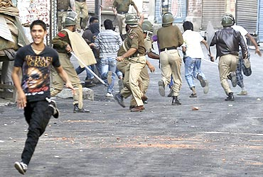 Police chase away Kashmiri protesters during an anti-India protest in Srinagar