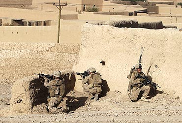US Marines and an Afghan National Policeman aim their weapons at Taliban positions