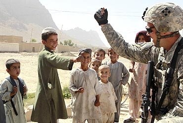 A US Army soldier gives a fist bump to residents in Kandahar province in Afghanistan