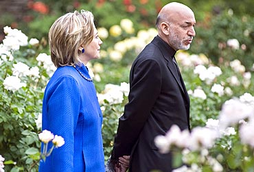 Karzai and US Secretary of State Hillary Clinton talk while walking in a private Georgetown garden in Washington