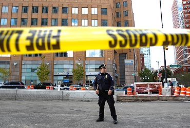 A New York policeman stands at the scene of a suspected bomb contained in a UPS package at a bank in Brooklyn