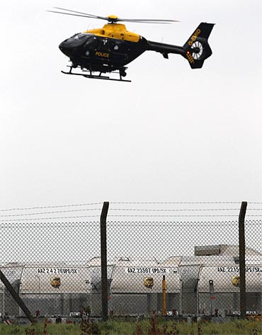 A police helicopter hovers over UPS containers at East Midlands Airport in Castle Donington, central England