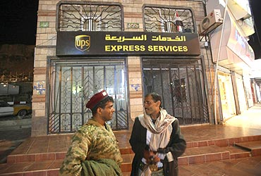 A soldier talks to a man in front of the UPS office in Sanaa, Yemen
