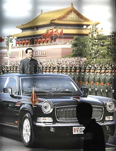 A visitor looks at a picture showing China's President Hu Jintao reviewing soldiers during a parade in front of Tiananmen Gate at the Chinese Military Museum in Beijing