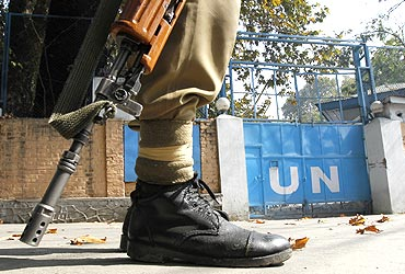 A policeman guards the main gate of the United Nations Military Observer Group during a curfew in Srinagar