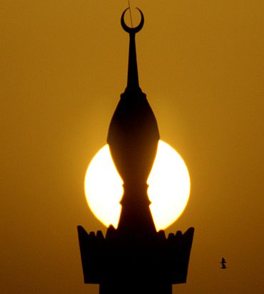 The sun sets behind a minaret in the centre of Riyadh