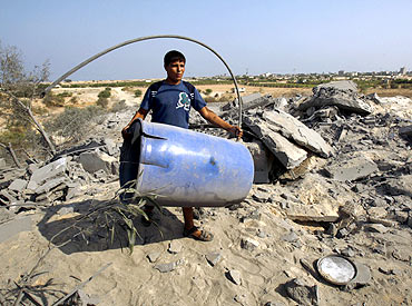A Palestinian carries a barrel at an abandoned house that was destroyed in an Israeli air strike in Deir al-Balah