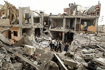 Palestinians survey houses damaged in an explosion in the central Gaza Strip
