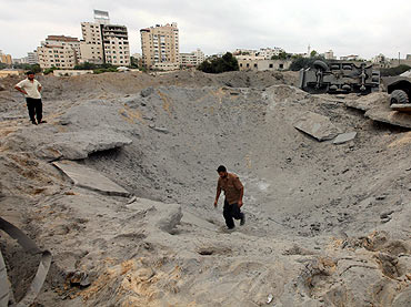 A member of Hamas' security forces surveys the damage after Israeli air strikes