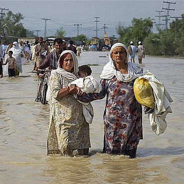 Two displaced Pakistani women wade through knee-deep water