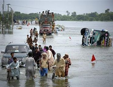 People wade through flood waters in Sindh