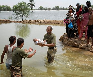 Pakistan army troopers transfer a baby to safety as others await their turn