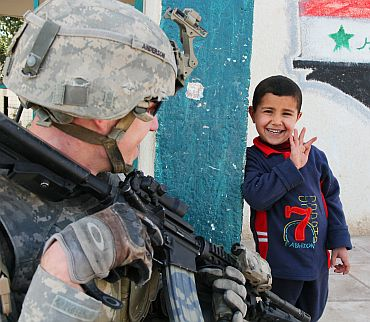 An Iraqi boy waves to a US soldier at the Al Tatawori school in Hor Albosch, Iraq