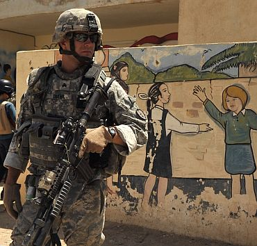 US Army Sgt David Diehl, from Alpha Company, 1st Battalion, 21st Infantry Regiment, provides security outside a school in Baqubah, Iraq