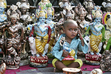 A boy plays with a mobile phone in front of idols of Lord Krishna