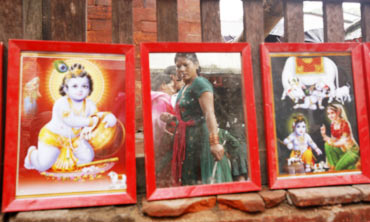 A devotee is reflected in a mirror next to pictures of Lord Krishna