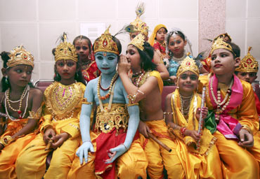 Children dressed as  Lord Krishna wait for a fancy dress competition